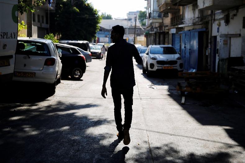 Teklit Michael, 29, an asylum seeker from Eritrea, is silhouetted as he walks home in Tel Aviv, Israel June 25, 2017.