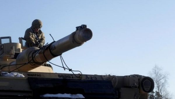 A U.S. soldier prepares for unload an M1 Abrams tank which will be deployed in Latvia for NATO