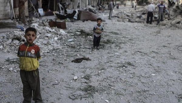 Children stand in the rubble of destroyed buildings in Syria.
