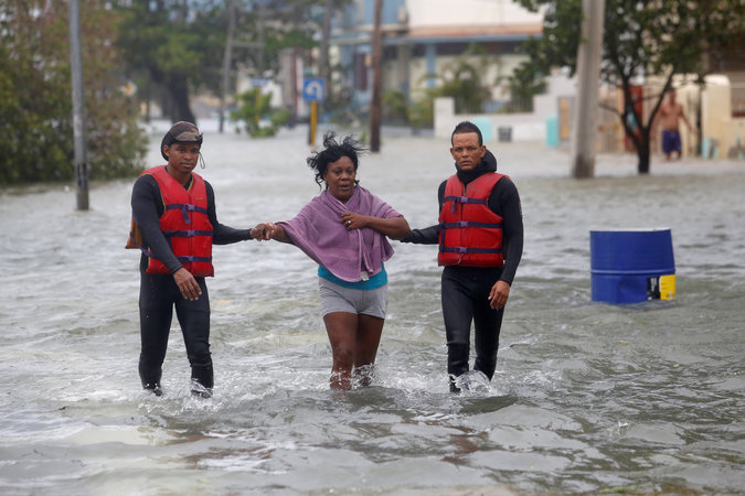 Rescue personnel help a woman