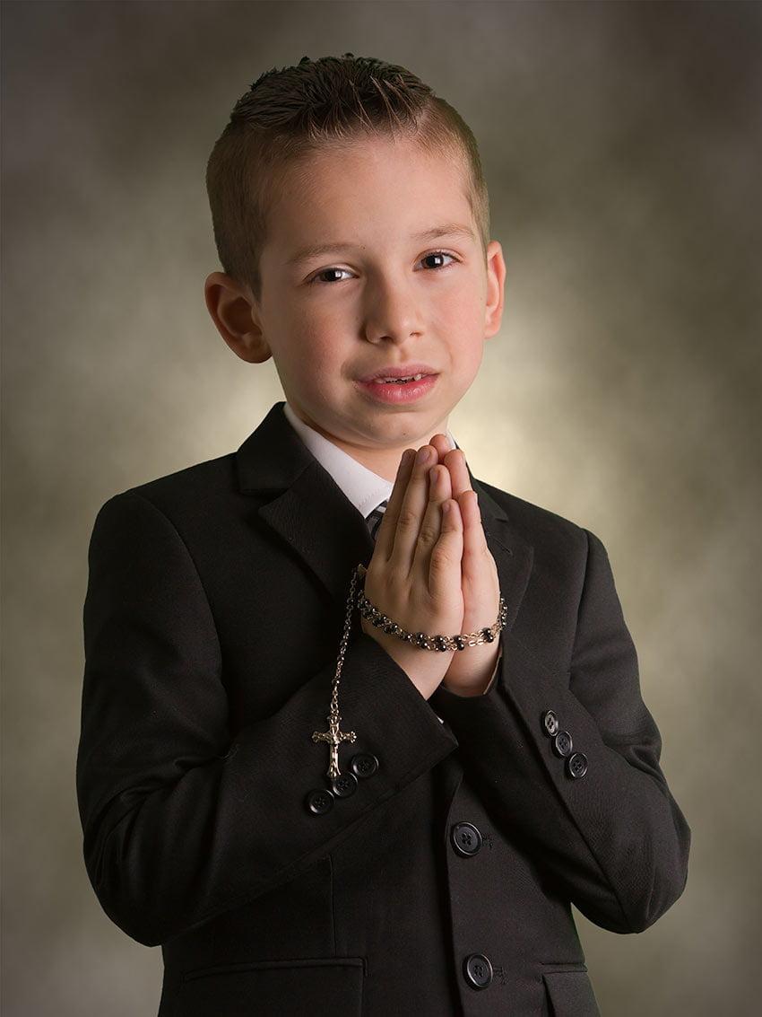 First communion praying boy holding cross