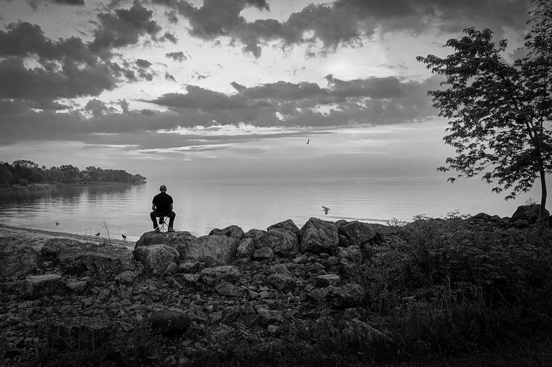 Man sitting by the lake alone watching sunset