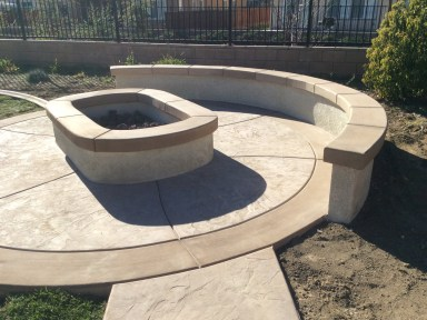 Fire pit with sitting wall and colored concrete in Menifee McCabe's Landscape Construction
