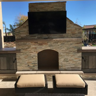 Outdoor fireplace with TV set and storage cabinets