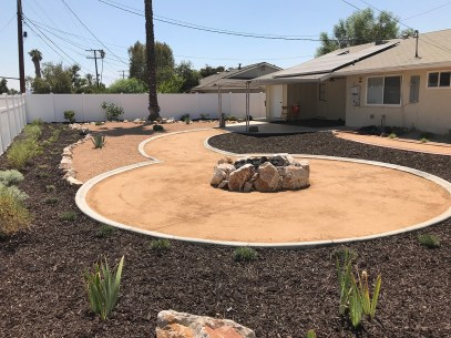 Low water backyard with boulder fire pit