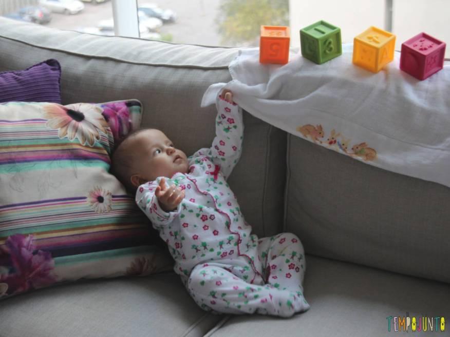 bebê puxa fralda para alcancar cubos