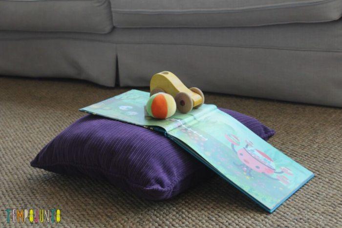 brinquedos do bebê de um jeito diferente - carrinho sobre livro