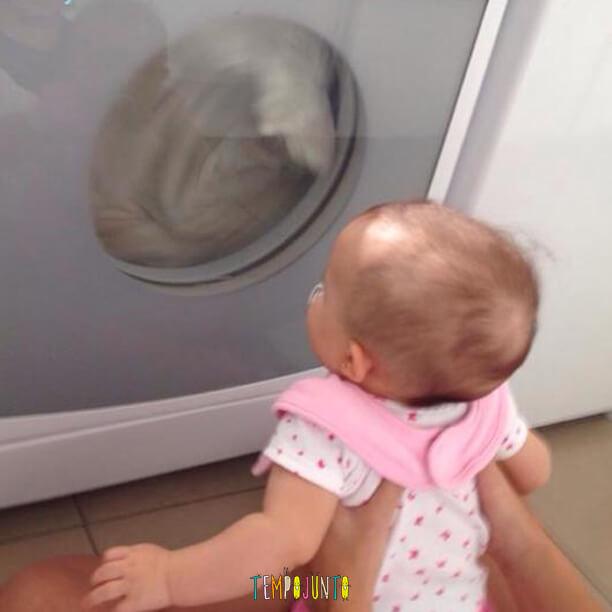 bebê se distrai olhando secadora de roupas funcionar