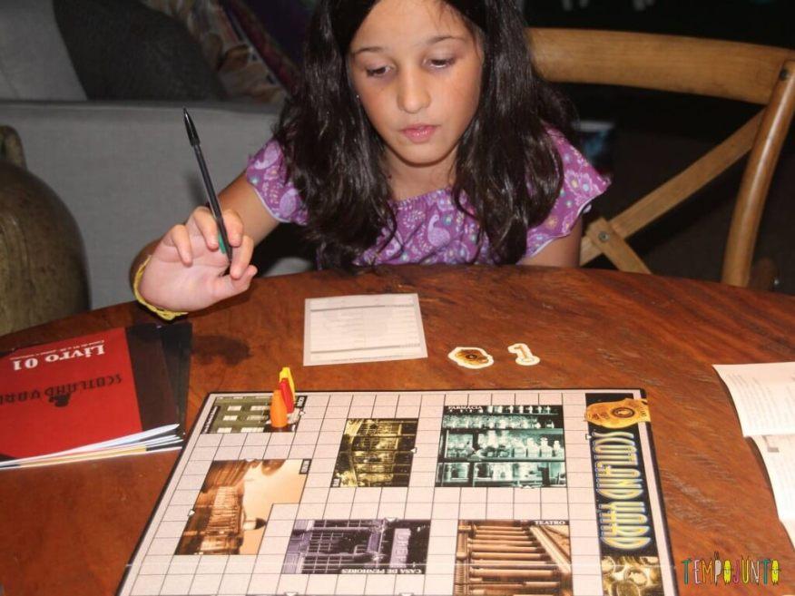 jogos em família - Carol brincando do jogo Scotland Yard