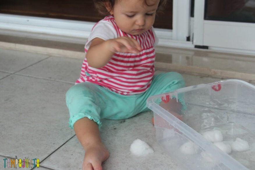 Brincadeira Sensorial com água e algodão para bebês - gabi jogando algodão no chão