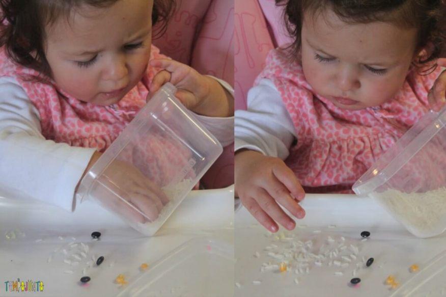 Brincadeira sensorial com grãos e papel contact - - Gabi pegando grao no pote