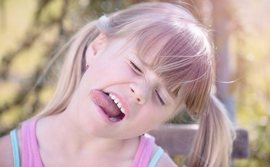 Brincadeira de trava-língua para estimular a fala - menina com a língua pra fora