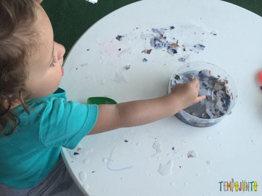 Brincadeira sensorial com papel picado - Gabi pegando o papel com a mão