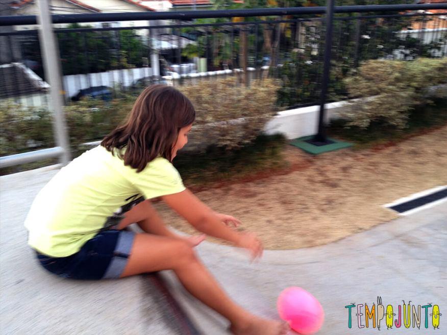 Uma bola uma rampa e a brincadeira ao ar livre está pronta - menina lançando a bola na rampa