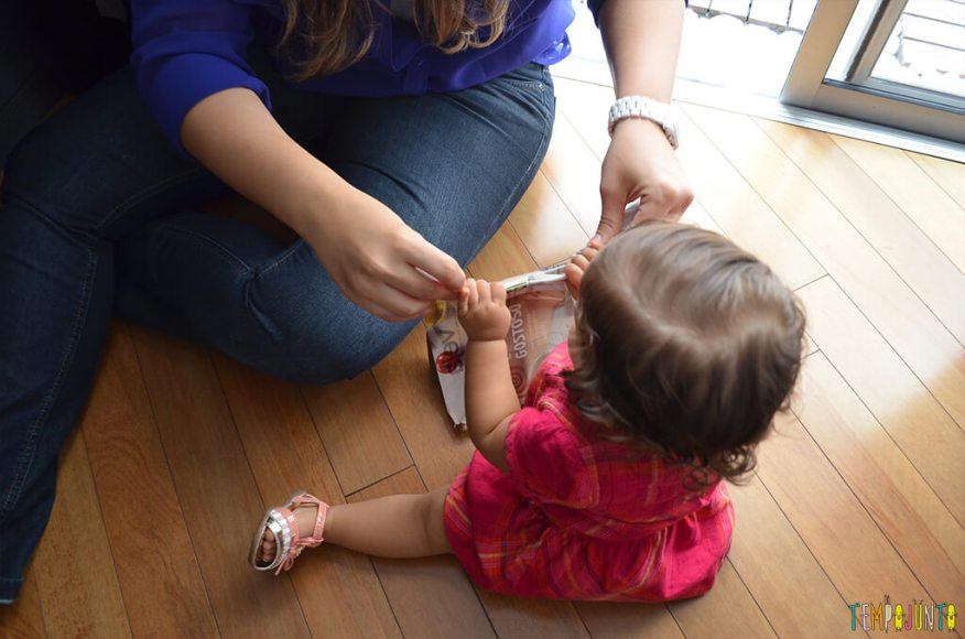 Brincadeira com o bebê usando folhas de revista - julia rasgando a revista com a mae