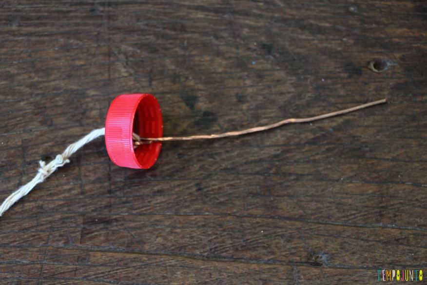 Como transformar tampas de garrafa em brinquedo - fio passando na tampinha