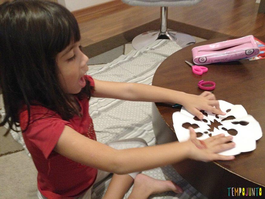 Arte para crianças entre 4 e 7 anos kirigami - larissa abrindo a dobradura pronta na mesa