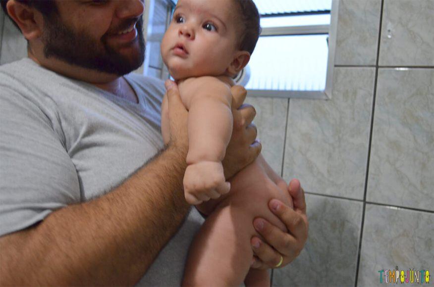 Brincadeira num banho calmante para o recém-nascido - bernardo no colo do pai