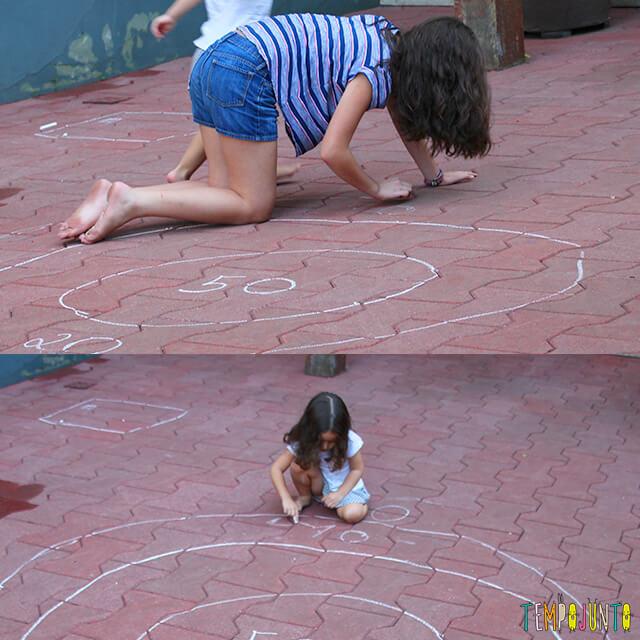 5 maneiras de brincar de acerte o alvo - meninas desenhando o alvo no chao
