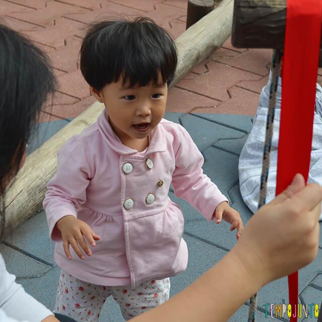 Despertar a curiosidade do bebê com uma brincadeira de causa e efeito - bebe olhando a roldana
