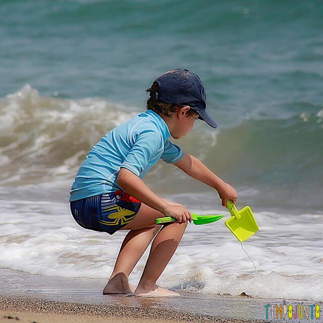 Dicas de estímulo sensorial e físico nas brincadeiras na praia - menino brincando na praia