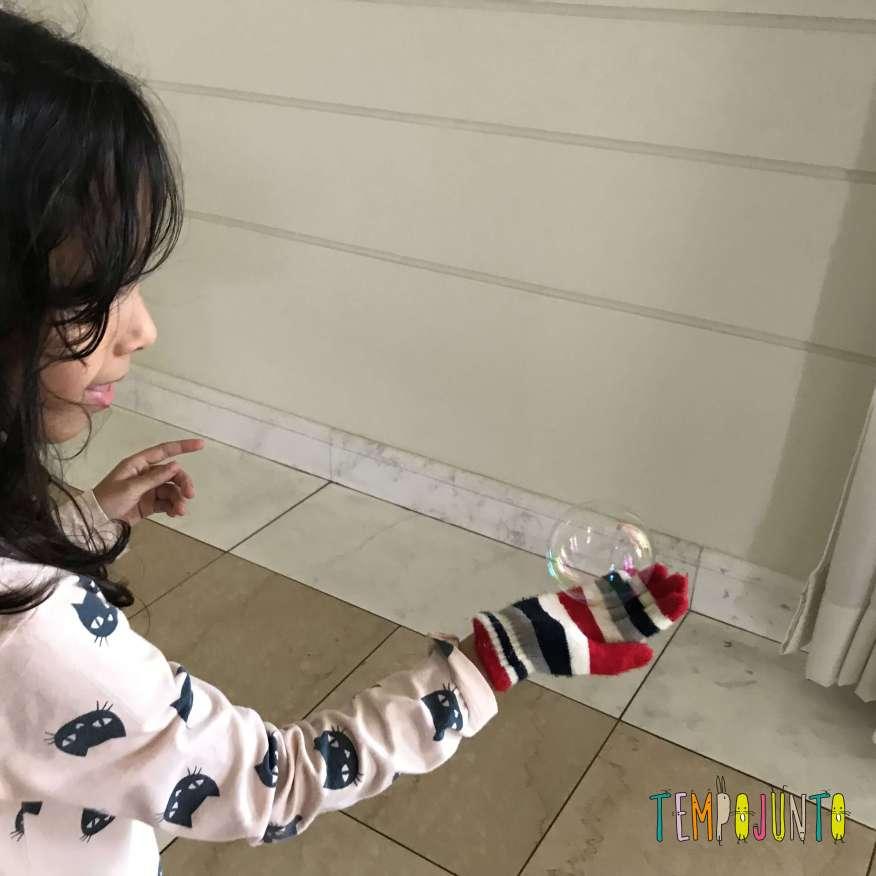 criança brincando com bolha de sabão e luva de lã