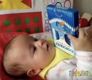 bebê explora caixa de cotonetes para brincar