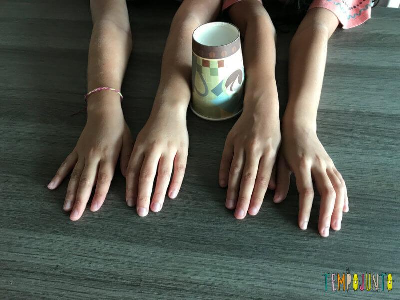 dois pares de mãos de meninas e um copo para o bate-mão e bate-copo
