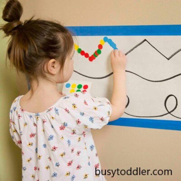 convite para brincar com menina colando etiquetas coloridas no papel