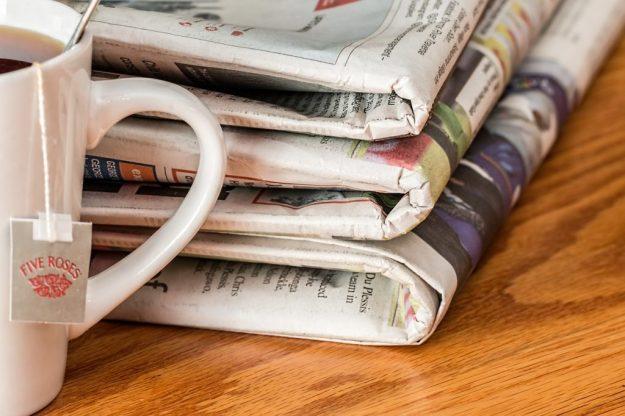 Newspaper pile and tea