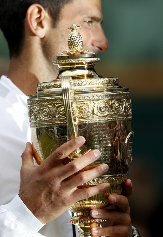 Novak Djokovic of Serbia celebrates with the trophy after winning against Roger Federer of Switzerland during their Men's final match for the Wimbledon Championships at the All England Lawn Tennis Club, in London, Britain, 14 July 2019. EPA-EFE/ADRIAN DENNIS / POOL EDITORIAL USE ONLY/NO COMMERCIAL SALES