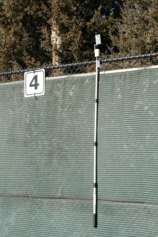 Tennis camera set up on fence