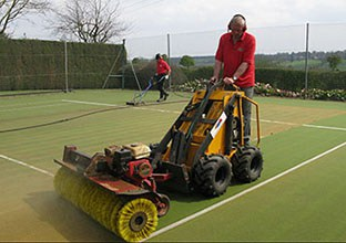 Brushing an En Tout Cas tennis court surface