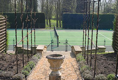 Tenis court fencing blends with garden landscaping