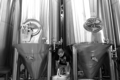 "Photo by Mario Bartel Jordan ""Chardonnay"" Wong fills a cask amidst the towering 3,000 litre stainless steel tanks."