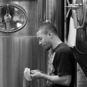 Photo by Mario Bartel Brew day is a frenetic dance of multitasking as beer is brewed, empty tanks are cleaned and kegs are filled for shipment. Wong refuels with a banana.
