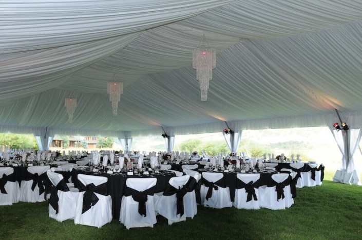 event rentals-Fabric Lined Tent With Chandeliers & Chair Covers With Sashes