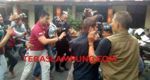 Nizar Romas (NR) menutupi wajahnya dengan koran saat dibawa petugas Polresta Bandarlampung.