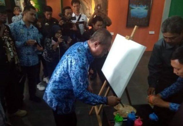 Wagub Bachtiar Basri mengggamar dengan kuas dan cat di atas kanvas pada pembukaan pameran seni rupa di Taman Budaya Lampung, Senin, 1 Oktober 2018.