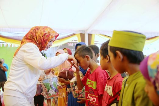 Ny. Riana Sari menyerahkan bingkisan kepada para anak yatim.