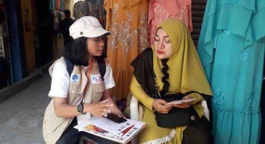 Relawan pandu digital sedang mambantu pedagang pakaian di Pasar Panjang membuat akun di marketplace.