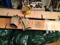 Wax, wood, gloves, drop cloth, and two chairs back-to-back for a table