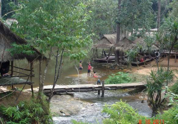 Bamboo thatched roof dwellings along the riverbank, waterfalls and rapids