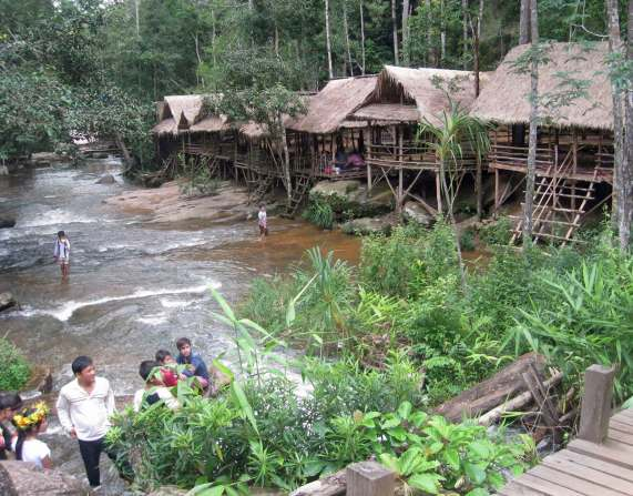 Thatched Bamboo shelters along a running stream with a waterfall and rapids,