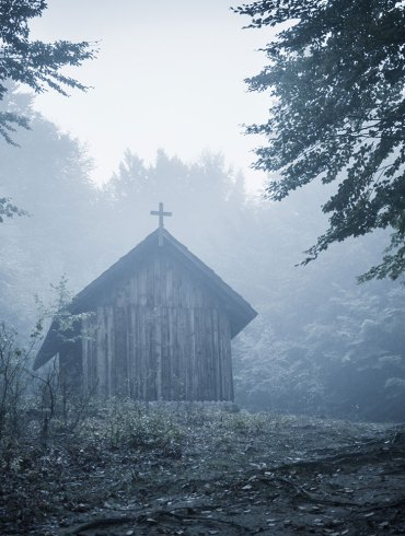 Old church in forest with fog