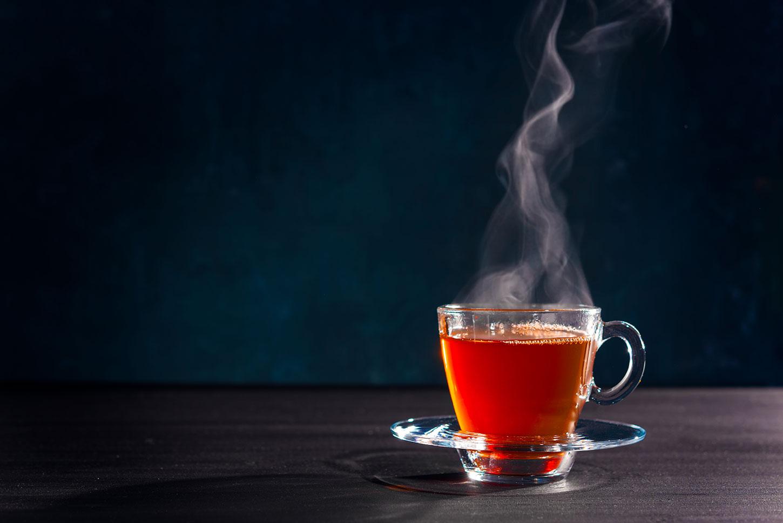 Steaming glass mug of tea