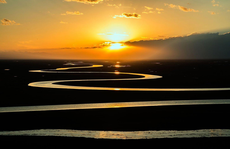 Sunset over winding river on prairie