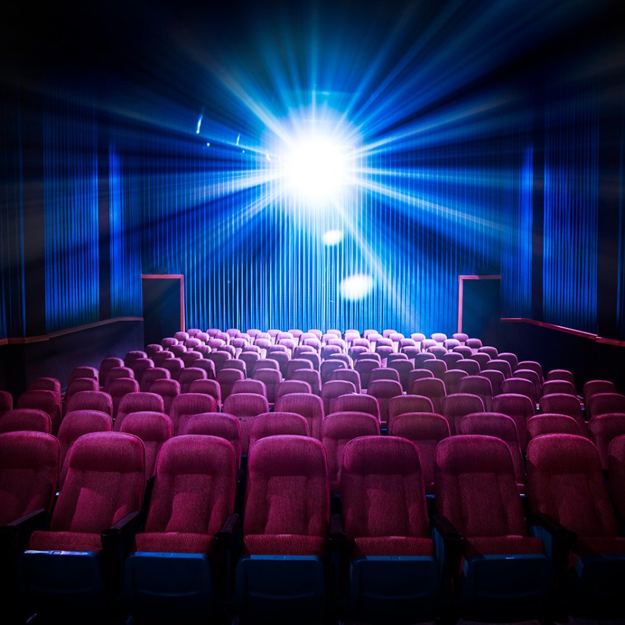 Movie theater with empty seats and projector light