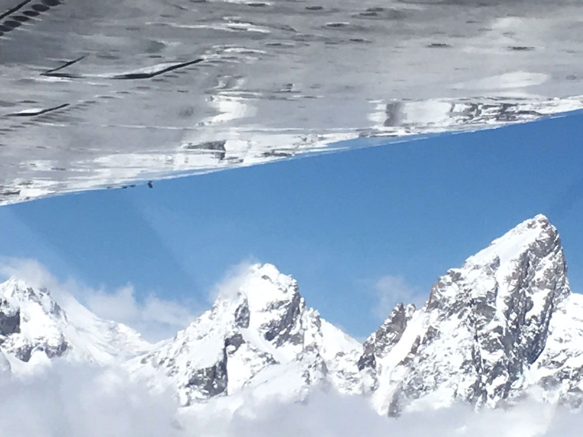 Aerial view of Grand Tetons and airplane wing