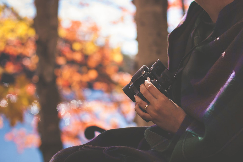Woman holding binoculars with autumn lake background